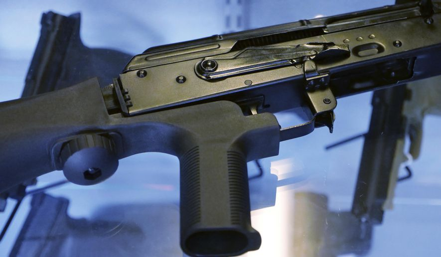 "In this Oct. 4, 2017, file photo, a device called a ""bump stock"" is attached to a semi-automatic rifle at the Gun Vault store and shooting range in South Jordan, Utah. In the days and weeks leading up to the ban on bump stocks that took effect Tuesday, March 26, 2019, tens of thousands of the devices were destroyed by owners or handed over to authorities. (AP Photo/Rick Bowmer, File)"