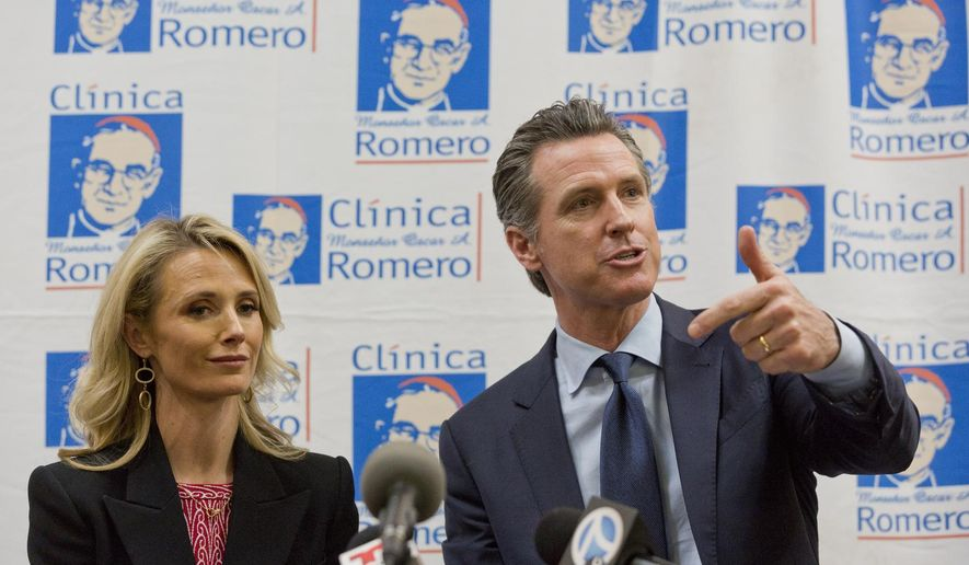 California Gov. Gavin Newsom with his wife, Jennifer Siebel Newsom attend a roundtable discussion with Central American community leaders at the Clinica Monsenor Oscar Romero in Los Angeles Thursday, March 28, 2019. Newsom said Thursday he will travel to El Salvador in April to discuss the poverty and violence that's causing waves of migrants to seek asylum in the United States. (AP Photo/Damian Dovarganes)