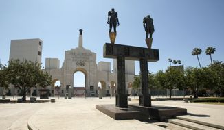 FILE - This July 1, 2009, file photo, shows the Los Angeles Memorial Coliseum with a pair of athlete statues installed for the 1984 Olympics, foreground, in Los Angeles.  The University of Southern California's sale of naming rights for Los Angeles Memorial Coliseum is being criticized as dishonoring the historic stadium's dedication as a memorial to soldiers who fought and died in World War I. USC announced last year that the stadium will be renamed United Airlines Memorial Coliseum as part of a $270 million renovation of the facility, which opened in 1923.  (AP Photo/Charlie Riedel)