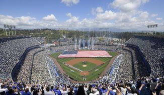 Fans stand for the national anthem before the opening day baseball game between the Los Angeles Dodgers and the Arizona Diamondbacks, Thursday, March 28, 2019, in Los Angeles. (AP Photo/Mark J. Terrill)