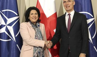 NATO Secretary General Jens Stoltenberg, right, and Georgian President Salome Zourabichvili shake hands for the media during their meeting in Tbilisi, Georgia, Monday, March 25, 2019. (AP Photo/Shakh Aivazov)