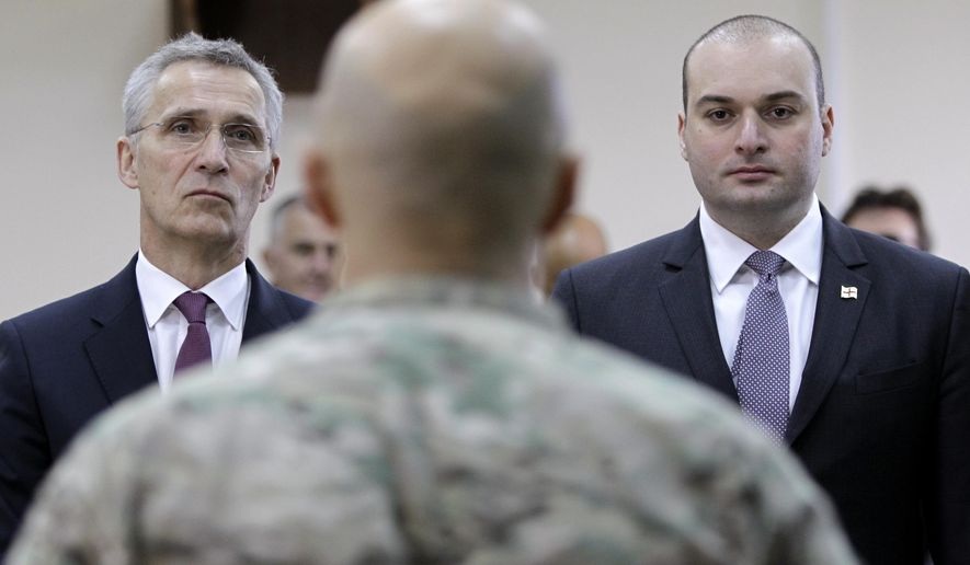 NATO Secretary-General Jens Stoltenberg and Georgian Prime Minister Mamuka Bakhtadze, right, meet with Georgian soldiers during multinational military exercises NATO - Georgia Exercise 2019, at the NATO-Georgia Joint Training and Evaluation Center in Krtsanisi, just outside Tbilisi, Georgia, Monday, March 25, 2019. (AP Photo/Shakh Aivazov)** FILE **