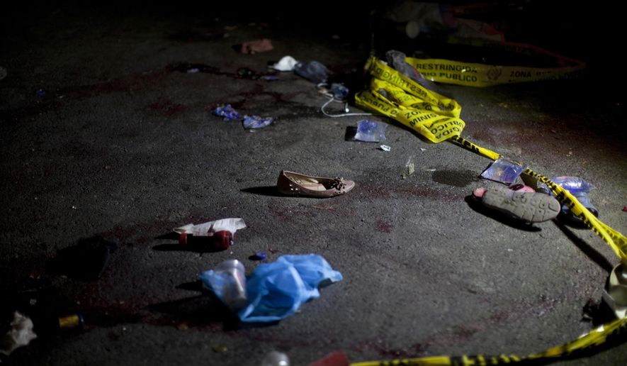 Yellow police tape and shoes lay on the ground in the place where an accident occurred, in Nahuala, Guatemala, early Thursday, March 28, 2019. A large truck slammed into a crowd gathered on a dark highway in western Guatemala, killing over a dozen people and leaving bodies scattered on the roadway, firefighters said. (AP Photo/Sandra Sebastian)