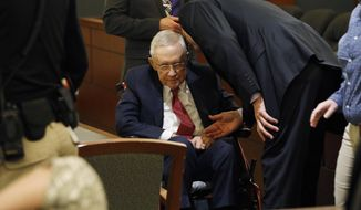 Former U.S. Sen. Harry Reid, center, sits in a wheelchair in court, Thursday, March 28, 2019, in Las Vegas. Reid testified in his negligence lawsuit against the maker of an exercise device. (AP Photo/John Locher)