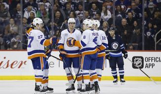 New York Islanders' Anders Lee (27), Brock Nelson, Ryan Pulock (6) and Josh Bailey (12) celebrate Lee's goal against the Winnipeg Jets during the second period of an NHL hockey game Thursday, March 28, 2019, in Winnipeg, Manitoba. (John Woods/The Canadian Press via AP)