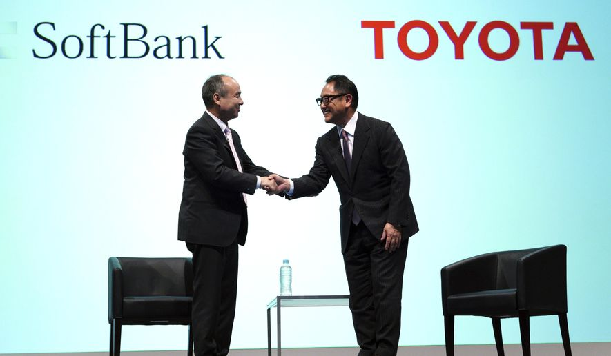 """FILE - In this Oct. 4, 2018, file photo, Softbank Group Corp. Chairman Masayoshi Son, left, and Toyota Motor Corp. President Akio Toyoda shake hands after their talk as part of a joint press conference in Tokyo. Japanese automakers Honda and Hino are joining a partnership between SoftBank and Toyota for mobility service innovation such as self-driving cars. SoftBank and Toyota, the nation's top automaker, announced a joint venture for mobility services, in what they called a """"united Japan"""" effort to face global competition. (AP Photo/Eugene Hoshiko, File)"""