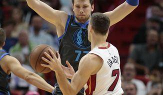 Dallas Mavericks forward Luka Doncic (77) defends against Miami Heat guard Goran Dragic (7) during the first half of an NBA basketball game, Thursday, March 28, 2019, in Miami. (AP Photo/Joel Auerbach)