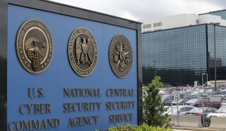 In this June 6, 2013 file photo, vehicles are parked near a sign outside the National Security Agency campus in Fort Meade, Md.    (AP Photo/Patrick Semansky, File)