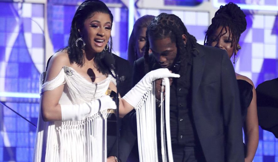 """FILE - This Feb. 10, 2019 file photo shows Cardi B, left, accepting the award for best rap album for """"Invasion of Privacy"""" as Offset kisses her hand at the 61st annual Grammy Awards in Los Angeles. The rapper has come under fire this week for what she says is a three-year-old video in which she claims she drugged men and robbed them. In the clip posted to Instagram Live, an emotional Cardi B explains in order to make it in the music industry _ and in life _ she had to do some things she is not proud of. (Photo by Matt Sayles/Invision/AP, File)"""