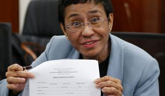 FILE - In this Feb. 13, 2019, file photo, Maria Ressa, the award-winning head of a Philippine online news site Rappler that has aggressively covered President Rodrigo Duterte's policies, shows an arrest form after being arrested by National Bureau of Investigation agents in a libel case in Manila, Philippines. Rappler Inc. reported on Friday, March 29, 2019, its CEO Ressa has been arrested again, this time over an alleged investment violation. (AP Photo/Bullit Marquez, File)