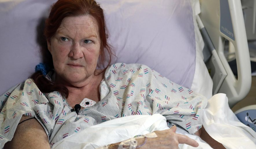 Deborah Judd, 56, sits in her hospital bed at Harborview Medical Center and talks about the injuries she suffered in a shooting a day earlier, Thursday, March 28, 2019, in Seattle. The afternoon shooting spree and carjacking in Seattle left two people dead and two injured. (AP Photo/Elaine Thompson)