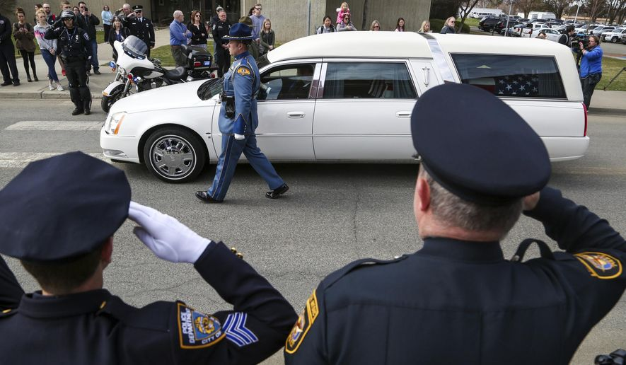 Law enforcement personnel salute as a hearse bearing the body of Kittitas County Deputy Sheriff Ryan Thompson arrives ahead of a memorial service at Central Washington University, Thursday, March 28, 2019, in Ellensburg, Wash. Hundreds of law enforcement officers from throughout the region have gathered for the memorial service for Thompson, who was shot to death by a road rage suspect last week. (Jake Green/The Daily Record via AP)