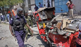 A policeman walks past a destroyed vehicle after an attack using an explosives-laden vehicle on a restaurant in Mogadishu, Somalia Thursday, March 28, 2019. Police say at least 10 people have been killed and others wounded in the car bomb blast outside the restaurant in the Somali capital. (AP Photo/Farah Abdi Warsameh) ** FILE **