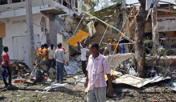 Somalis walk near wreckage at the scene following an attack outside a restaurant in Mogadishu, Somalia Thursday, March 28, 2019.  An explosives-laden vehicle detonated outside a busy restaurant in Somalia's capital, killing at least 10 people, police said Thursday. (AP Photo/Farah Abdi Warsameh) ** FILE **