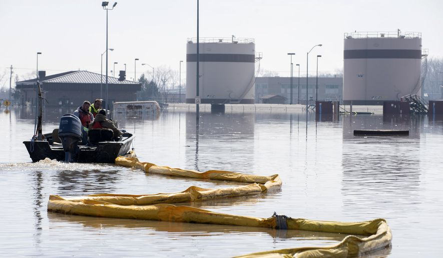 In this March 18, 2019, photo released by the U.S. Air Force, environmental restoration employees deploy a containment boom from a boat on Offutt Air Force Base in Nebraska, as a precautionary measure for possible fuel leaks in the flooded area. After massive flooding along the Missouri River in the spring of 2019, many want to blame the agency that manages the river's dams for making the disaster worse, but it may not be that simple. The U.S. Army Corps of Engineers says much of the water that created March's flooding came from rain and melting snow that flowed into the river downstream of all the dams, and at the same time, massive amounts of water filled the reservoirs and some had to be released. (Delanie Stafford/U.S. Air Force via AP) **FILE**