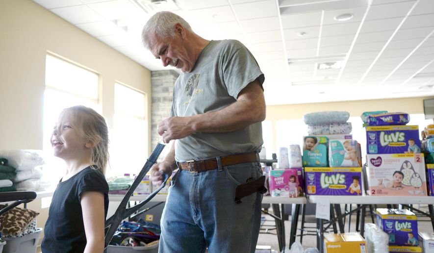 """Larry Poell, who lives on top of a Superfund site in Mead, Neb., adjusts Wednesday, March 27, 2019, the overalls of his granddaughter, while visiting a flood relief shelter in Ashland. Poell said federal officials have always maintained that the contaminated plumes are stable, but he wonders if the floodwater caused them to shift. """"I'm concerned about it, I think everybody's concerned about it,"""" he said.   (AP Photo/Nati Harnik)"""