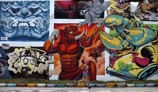 Thai woman runs past graffiti at a public park Bangkok, Thailand Thursday, March 28, 2019. As Thais wait for official results of their general election, political parties led by one ousted from power in a military coup say they believe they have won enough seats to form the next government. (AP Photo/Sakchai Lalit)