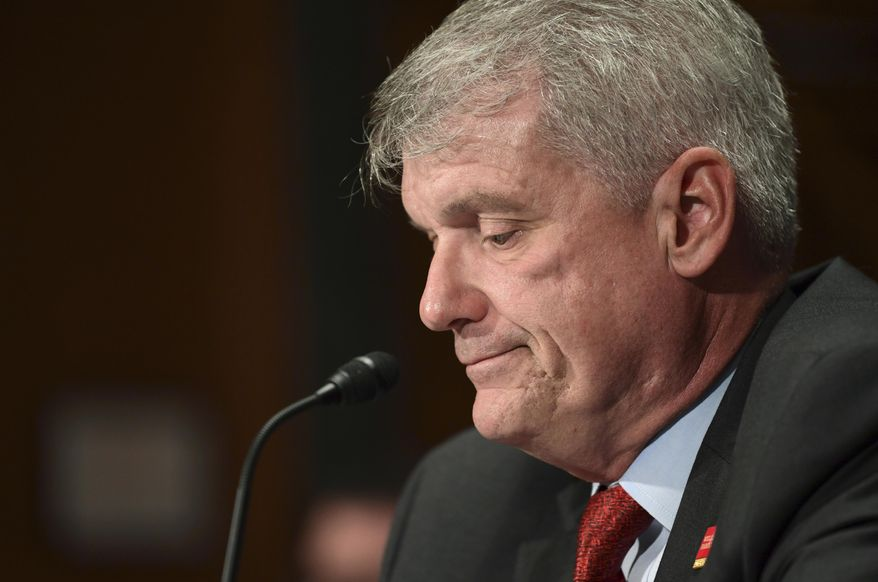 FILE- In this Oct. 3, 2017, file photo Wells Fargo Chief Executive Officer and President Timothy Sloan looks down as Sen. Elizabeth Warren, D-Mass., questions him as he testifies before the Senate Committee on Banking, Housing and Urban Affairs on Capitol Hill in Washington. Sloan stepped down on Thursday, March 28, 2019, effective immediately, after less than four years on the job during which the deeply troubled bank dealt with a seemingly unending wave of scandals. (AP Photo/Susan Walsh, File)