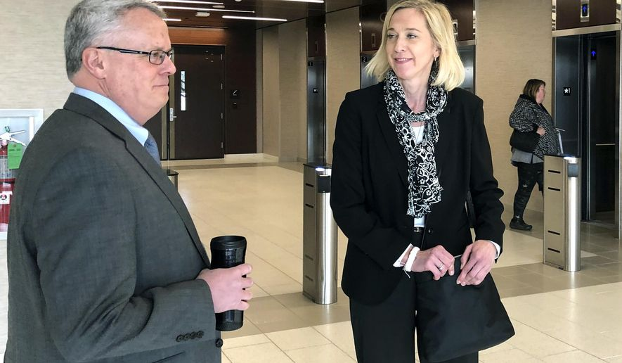 Former Wisconsin Public Service Commission Chairwoman Ellen Nowak right, and her former assistant, Bob Seitz, stand outside the entrance to the PSC's headquarters after being stopped by a security guard in Madison, Wisc., Thursday, March 28, 2019. Nowak was one of 82 former Republican senators appointed by Gov. Scott Walker and confirmed in a lame-duck session in December. A Dane County judge ruled last week the session was illegal and Democratic Gov. Tony Evers rescinded all the appointments. A state appeals court stayed that ruling on Wednesday. (AP Photo/Todd Richmond)