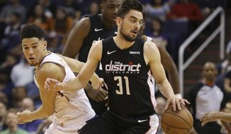 Washington Wizards guard Tomas Satoransky (31) is fouled by Phoenix Suns Devin Booker, left, as Wizards' Thomas Bryant, back, watches during the first half of an NBA basketball game Wednesday, March 27, 2019, in Phoenix. (AP Photo/Ross D. Franklin) ** FILE **