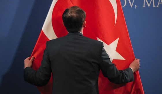A man sets up a Turkish flag before press statements by Turkish Vice President Fuat Oktay and Romanian Prime Minister Viorica Dancila in Snagov, Romania, Friday, March 29, 2019. (AP Photo/Vadim Ghirda)