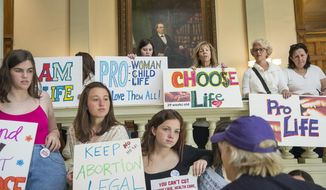 "File-This March 22, 2019, file photo shows, pro-abortion rights and anti-abortion demonstrators displaying their signs in the lobby of the Georgia State Capitol building during the 35th legislative day at the Georgia State Capitol building in downtown Atlanta.  Bucking intense opposition from abortion rights groups, citizens, physicians groups and even Hollywood celebrities, Georgia lawmakers gave final approval Friday, March 29, 2019, to a ""heartbeat"" abortion ban that would outlaw almost all abortions in the state. The proposal now heads to the desk of Republican Gov. Brian Kemp, who backs it. If enacted, it would be among the strictest abortion bans in the U.S. (Alyssa Pointer/Atlanta Journal-Constitution via AP, File)"