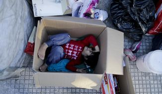 In this Feb. 25, 2019 photo, Nicole Aleman lies inside a box on the street where she lives with her family in Buenos Aires, Argentina. A makeshift tent of cardboard and plastic bags on the side of a busy avenue in the Argentine capital serves as the shelter for the girl, her four siblings and her parents, who sleep sharing two old mattresses laid out on the concrete. (AP Photo/Natacha Pisarenko)