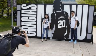 San Antonio Spurs fans pose for a photo in front of a sign thanking Spurs legend Manu Ginobili before an NBA basketball game against the Cleveland Cavaliers, Thursday, March 28, 2019, in San Antonio. Ginobili's jersey will be retired after the game. (AP Photo/Darren Abate)