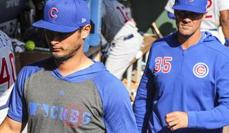 Chicago Cubs' pitchers Yu Darvish (11) and Cole Hamels (35), former Rangers' pitchers leave the dugout during the baseball game against the Texas Rangers Thursday, March 28, 2019 in Arlington, Texas. (AP Photo/Richard W. Rodriguez)
