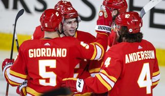 Calgary Flames' Sean Monahan (23) celebrates his goal with teammates during the second period of the team's NHL hockey game against the Anaheim Ducks on Friday, March 29, 2019, in Calgary, Alberta. (Jeff McIntosh/The Canadian Press via AP)