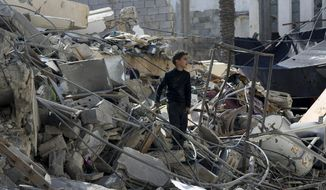 A Palestinian boy searches for their family's belongings amid the rubble of a destroyed building near a Hamas security building that was destroyed in an Israeli airstrike late Monday, in Gaza City, Wednesday, March 27, 2019. (AP Photo/Adel Hana)