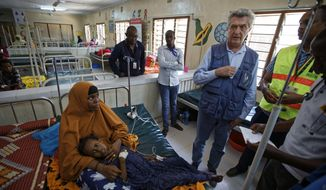 FILE - In this Tuesday, Dec. 19, 2017 file photo, U.N. refugee chief Filippo Grandi, center-right, visits a hospital as he tours Dadaab refugee camp, hosting over 230,000 inhabitants, in northern Kenya. An internal United Nations document obtained by The Associated Press on Friday, March 29, 2019 says Kenya again seeks to close the Dadaab camp that hosts more than 200,000 refugees from neighboring Somalia. (AP Photo/Ben Curtis, File)