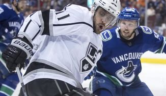 Los Angeles Kings' Anze Kopitar (11), of Slovenia, reaches for the puck in front of Vancouver Canucks' Alex Biega during the third period of an NHL hockey game Thursday, March 28, 2019, in Vancouver, British Columbia. (Darryl Dyck/The Canadian Press via AP)