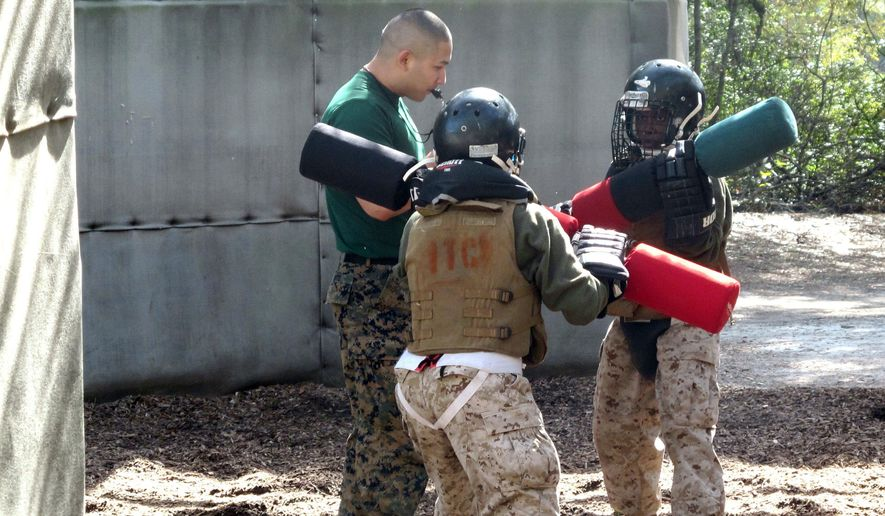In this Feb. 21, 2013, file photo, female recruits battle with pugil sticks during training at the Marine Corps Training Depot on Parris Island, S.C. (AP Photo/Bruce Smith, File)