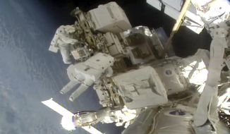This photo provided by NASA, astronauts Nick Hague and Christina Koch float outside the International Space Station, Friday, March 29, 2019, a week after the first spacewalk to install new and stronger batteries for the station's solar power grid.  Koch was supposed to go out with Anne McClain, but there weren't enough medium suits readily available. So the first all-female spacewalk had to be scrapped.   (NASA via AP)