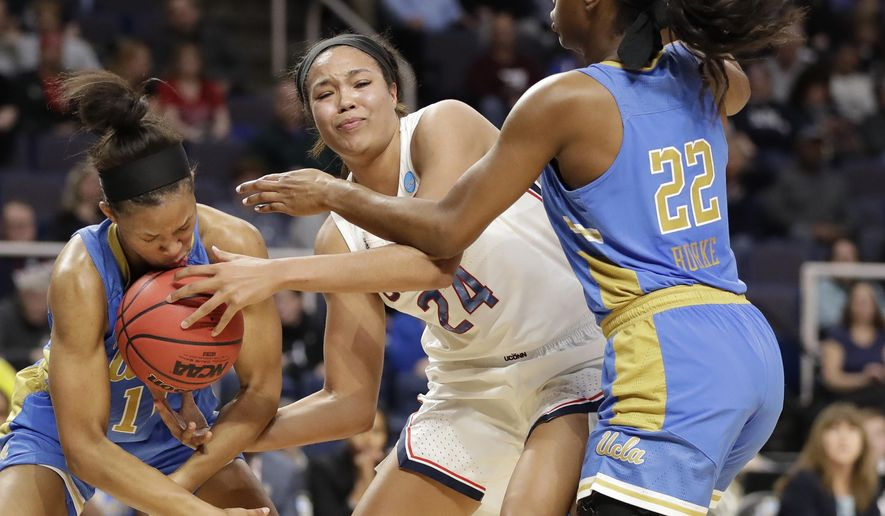 UCLA forward Lajahna Drummer, left, gets the basketball to her face as she tries to steal the ball from Connecticut forward Napheesa Collier (24) with UCLA guard Kennedy Burke (22) defending during the first half of a regional semifinal game in the NCAA women's college basketball tournament, Friday, March 29, 2019, in Albany, N.Y. (AP Photo/Kathy Willens)