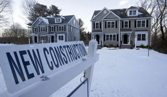 FILE- In this Feb. 21, 2019, file photo a newly constructed homes sit near a sign in Natick, Mass. On Friday, March 29, the Commerce Department reports on sales of new homes in February. (AP Photo/Steven Senne, File)