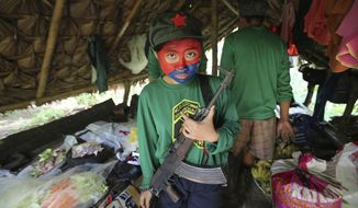 FILE - In this Nov. 23, 2016 photo, a woman New People's Army guerrilla with her face painted to conceal her identity holds her firearm inside a shelter at a rebel encampment tucked in the harsh wilderness of the Sierra Madre mountains, southeast of Manila, Philippines. Communist guerrillas are marking half a century of their rural rebellion in the Philippines with threats of more attacks, possibly spreading into cities, as a negotiated settlement remained elusive with peace talks repeatedly stalling. (AP Photo/Aaron Favila, File)