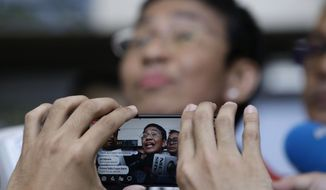 Rappler CEO and Executive Editor Maria Ressa is recorded on a smartphone as she talks to reporters after posting bail at the Pasig Regional Trial Court, metropolitan Manila, Philippines on Friday March 29, 2019. The head of a Philippine online news site, among media agencies deemed critical of Philippine President Rodrigo Duterte, was arrested again Friday, this time over an alleged investment violation. (AP Photo/Aaron Favila)