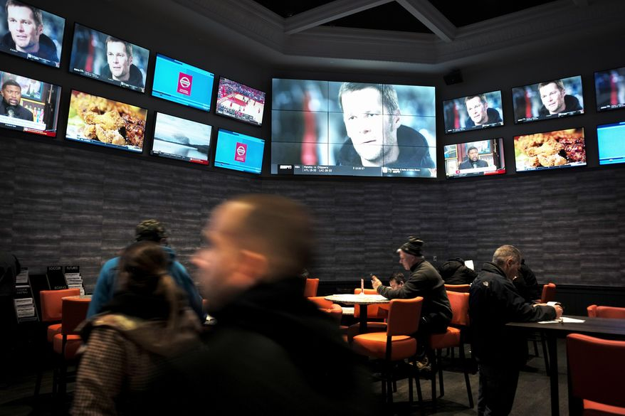 FILE - In this Monday, Jan. 28, 2019 file photo, patrons visit the sports betting area of Twin River Casino in Lincoln, R.I. The state lottery released figures on Friday, March 29, 2019, showing that casinos in Rhode Island lost nearly $900,000 on sports betting in February, after they paid out winning bets for the Super Bowl and other professional sports. ( AP Photo/Steven Senne, File)