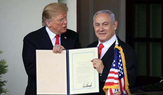 Visiting Israeli Prime Minister Benjamin Netanyahu and President Donald Trump hold up the signed proclamation recognizing Israel's sovereignty over the Golan Heights as Netanyahu leaves the White House in Washington, Monday, March 25, 2019. (AP Photo/Manuel Balce Ceneta)