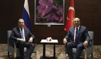 Turkey's Foreign Minister Mevlut Cavusoglu, right, and his Russian counterpart Sergey Lavrov pose for photographs prior to their meeting in the Mediterranean coastal city of Antalya, Turkey, Friday, March 29, 2019. The two ministers attending the Turkey - Russia Joint Strategic Group Meeting comes ahead of municipal elections scheduled to be held across Turkey on Sunday March 31. (Turkish Foreign Ministry via AP, Pool)