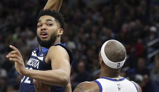 Minnesota Timberwolves' Karl-Anthony Towns passes the ball behind his head as Golden State Warriors' DeMarcus Cousins defends during the first half of an NBA basketball game Friday, March 29, 2019, in Minneapolis. (AP Photo/Stacy Bengs)