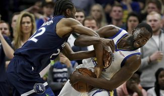 Golden State Warriors' Draymond Green fights for possession of the ball against Minnesota Timberwolves' Andrew Wiggins during the second half of an NBA basketball game Friday March 29, 2019, in Minneapolis. Minnesota won 131-130 in overtime. (AP Photo/Stacy Bengs)