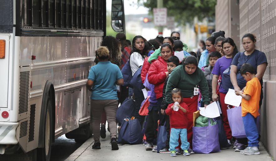 In this Friday, March 29, 2019 photo, migrants released from Texas detention centers arrive by the bus loads at the San Antonio bus station. (Bob Owen/The San Antonio Express-News via AP)