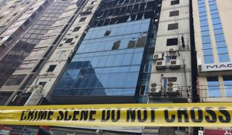 CORRECTS PHOTOGRAPHER'S NAME - A high-rise office building damaged by Thursday's fire is pictured in Dhaka, Bangladesh Friday, March 29, 2019. A Bangladeshi housing official said Friday criminal charges would be filed against the owner of the building where a fire killed dozens of people and which had four upper floors constructed illegally.(AP Photo/Al-emrun Garjon)