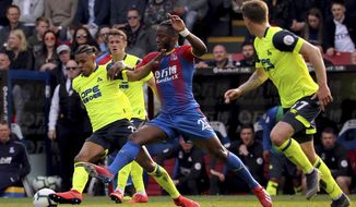 Huddersfield Town's Juninho Bacuna, left, and Crystal Palace's Michy Batshuayi tussle for the ball during the English Premier League soccer match between Crystal Palace and Huddersfield at the Selhurst Park stadium, London. Saturday, March. 30, 2019 (Isabel Infantes/PA via AP)