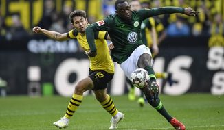 Wolfsburg's Jerome Roussillon, right, and Dortmund's Raphael Guerreiro challenge for the ball during the German Bundesliga soccer match between Borussia Dortmund and VfL Wolfsburg in Dortmund, Germany, Saturday, March 30, 2019. (AP Photo/Martin Meissner)