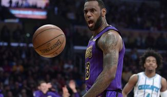 Los Angeles Lakers forward LeBron James, left, yells after dunking as Charlotte Hornets guard Devonte' Graham watches during the first half of an NBA basketball game Friday, March 29, 2019, in Los Angeles. (AP Photo/Mark J. Terrill) ** FILE **