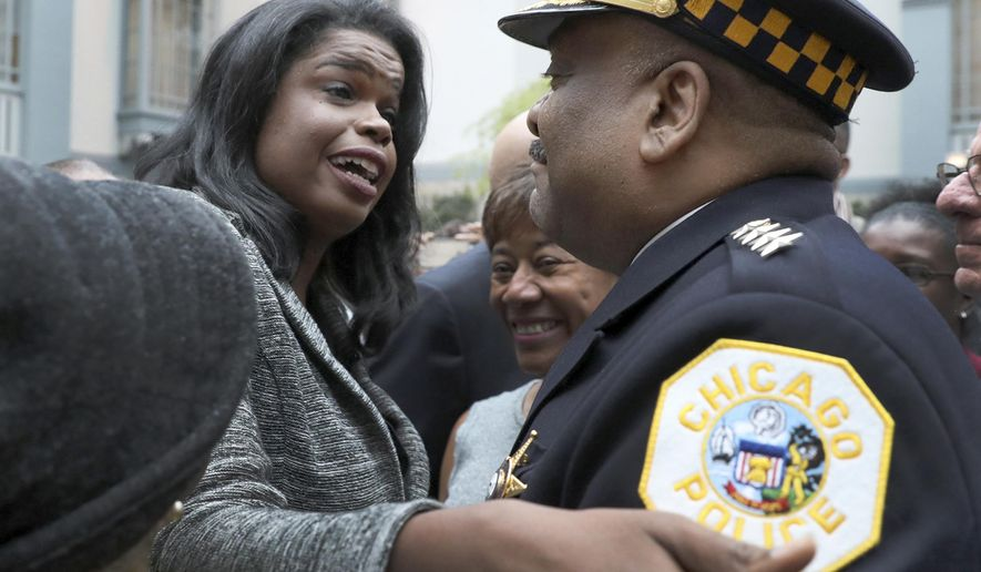 Kim Foxx, left, greets Police Superintendent Eddie Johnson at her swearing in ceremony as the new Cook County State's Attorney in Chicago. (Nancy Stone/Chicago Tribune via AP, File)